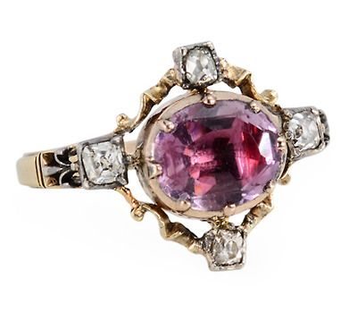 Late 18th century ring of 15k yellow gold and silver provides a radiant example of the detailed and fine craftsmanship of Georgian jewelry. An oval faceted amethyst has been foiled and claw set closed back in a yellow gold crimped collet. The amethyst gem with pink and lilac hues appears to be floating within an openwork frame of lightly twisted gold work accented at the each cardinal points with an old mine cut diamond in a square rub-over silver collet. Circa 1780
