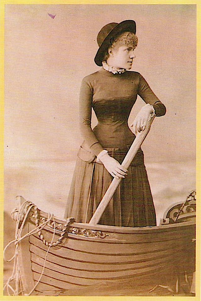 Eulalia wears an early 1880s dress with a pronounced A-line skirt with frills showing at her neckline and sleeve openings in this photo.