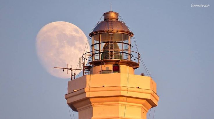 Salento, dietro al faro spunta una luna gigante