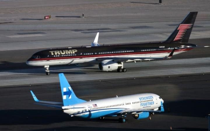 Republican presidential nominee Donald Trump's plane (TOP) passes Democratic presidential nominee Hillary Clinton's campaign plane at McCarran International Airport in Las Vegas, Nevada, on the eve of the two candidates' third and final US presidential debate