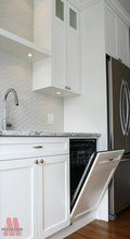 custom dishwasher hidden in white cabinetry with stainless steel appliances