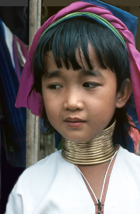 Young Padaung girl starts wrapping copper coils around her neck so she can become a tourist attraction like her female relatives