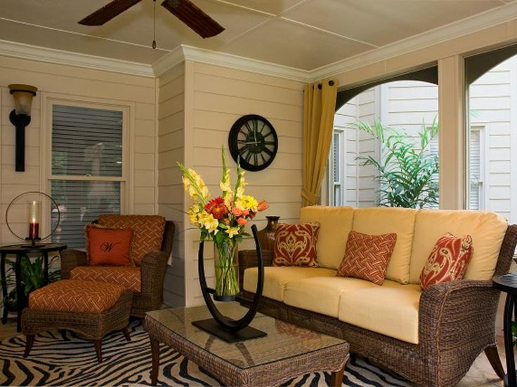 Wicker furniture and paneled walls create a breezy country style in this covered patio. A zebra-striped rug adds a cheeky, contemporary touch.