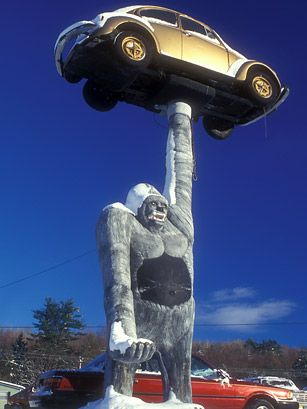 Gorilla holding a VW Bug;  Leicester, VT;  the statue was made by T. J. Neil for Pioneer Auto Sales;  customers can sit in the right hand of the gorilla...