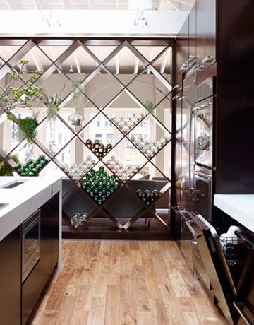 The room divider doubles as a wine rack and was custom-made by KraftMaid. Push a button and the 24-inch Jenn-Air microwave (under the island counter) opens like a drawer, for easy access. The Jenn-Air TriFecta dishwasher has a top-rack-only option, to save energy. - HouseBeautiful.com
