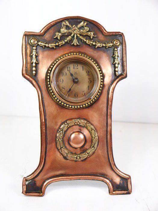 Fraai rood met geel koperen staand tafelklokje met een mechanisch Junghans uurwerk.  In mooie, goed functionerende conditie.   Afmetingen: Hoogte: 18,5 cm Breedte: 12 cm Diepte: 11 cm  Aangetekende verzending.