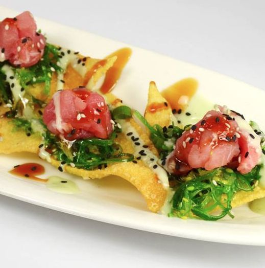 Bokamper's Sports Bar & Grill serves sushi with a twist - lightly seared tuna atop crispy wonton chips and add wakame (japanese seaweed salad), scallions and sesame seeds, served with teriyaki, sriracha and wasabi sauce for a dish that is savory, spicy, and crunchy.
