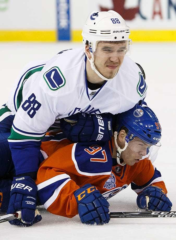 Connor McDavid of the Edmonton Oilers is flattened by Nikita Tryamkin of the…