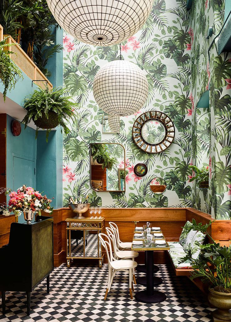Tropical interior design for an Oyster Bar in San Francisco. Tropical wallpaper juxtaposed with a bold checkered floor and gold accents to glamorise the look.