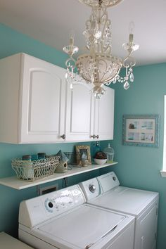 Maybe this will make me want to do laundry...Lovely laundry room CM: Love everything about this. The chandelier to make laundry doing fabulous, the Tiffany blue wall, and the little shelf to mask the fact that the washer and dryer aren't flush with the wall (I've always hated that). Fantastic!