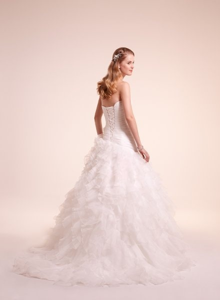 7813    Organza draped gown with ruffled skirt and flral applique at hip