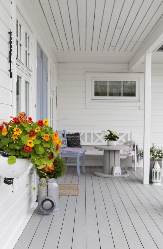 UNDER TAK: Et overbygget inngangsparti er hyggelig å komme hjem til, og er det stort nok, kan du bruke det til en sittekrok. Her er en benk og en gammel trommel sammen med en blåmalt stol et særegent møblement, med god plass til ettermiddagssol-kos. En stor bøtte med blomkarse tilfører herlig farge.