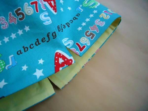 """裏付きの巾着袋をきれいに作る方法についてのご質問をいただきましたので、 私のやり方をご紹介します。   こちらのお子様用お弁当袋を作る手順で以下ご紹介します。  それでは行ってみよー!      私は、同じサイズのものをたくさん作るので、写真のように型紙を作っています。 今回の型紙は25センチ四方です。 型紙用方眼紙を使うと便利です。   1.生地の底を""""わ""""にして二つ折りにして型紙を置く。   私はまち針でとめますが、プロはまち針は使わないそうです。  2.上・左右の縫い代1センチで裁断。  3.生地の間に両面チャコペーパーをはさんでルレットで印をつける。   周囲をぐるっと一周、5センチおきに印をつけておくと、あとで縫いやすい。   ★裏地も同様の作業をする。      4.左写真のように、底のマチになる部..."""