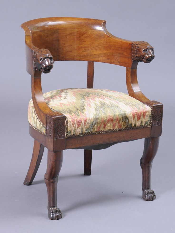 EMPIRE CARVED MAHOGANY FAUTEUIL EN BUREAU The curved top rail with lion head terminals, and the D-shape seat on rails with anthemion, raised on lion legs ending in paw feet. Provenance: Property from a Private Collector. 32 3/4 x 24 in. Estimate $ 2,000-3,000