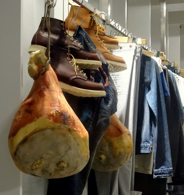 Parma ham and clothes for sale side by side in a store in Parma, Italy