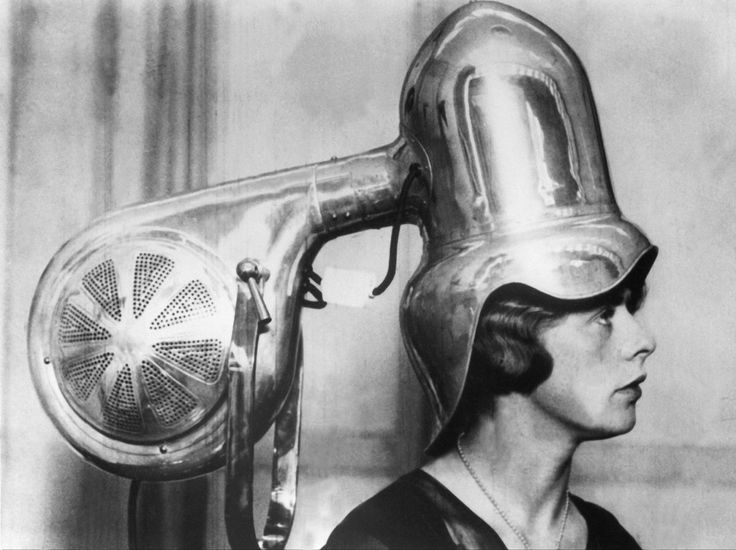 A woman sits under a chrome-plated hair dryer 1928