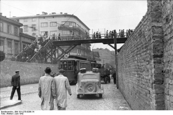 Warsaw Ghetto, June 1942: The Jews were walled in and isolated from the rest of Warsaw. Chl'odna Street (looking West) from the intersection with Zi‡elazna Street. The street was Aryan and above the street one can see a wooden bridge connecting the Small and Big Ghetto's.