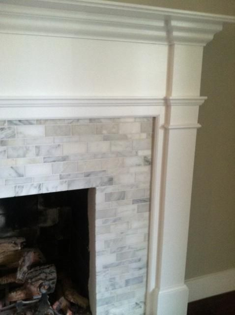 Clean look on the trim! Ok this is too expensive, but like this?  Fireplace mantle and surround - hand cut, custom pattern tile (Calcutta gold marble)