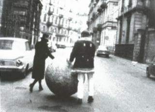 Film still of Michelangelo Pistoletto in 1967 on a street in Turin with Palla di giornali (Oggetti in meno) (Ball of newspapers [Minus objects]) 1966