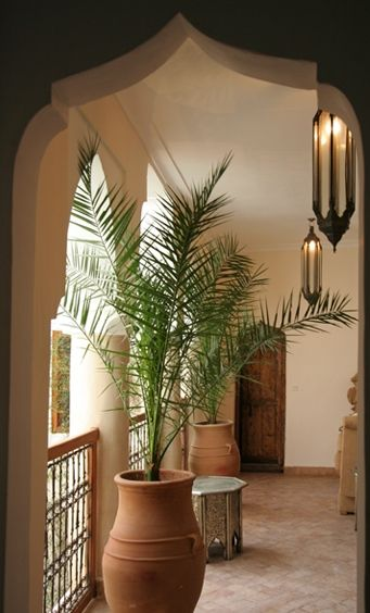 Love the plants and Arabian side table. Pretty doorway too.