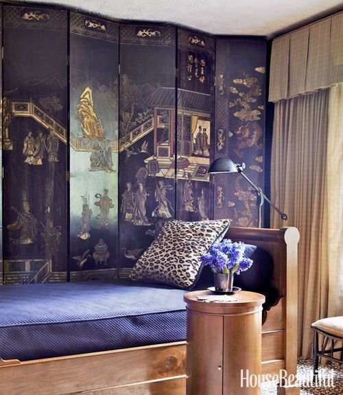 A Coromandel screen takes center stage in this elegant guest room with a sleek day bed and leopard rug and pillows