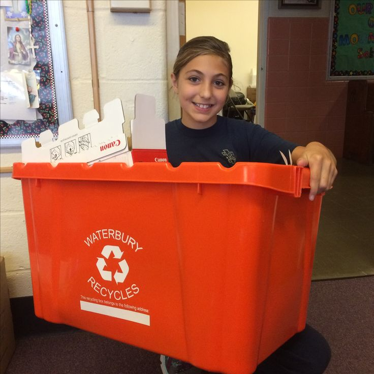 Sydney Jason shows off a full recycling bin, part of her recycling efforts at Our Lady of Mount Carmel School.