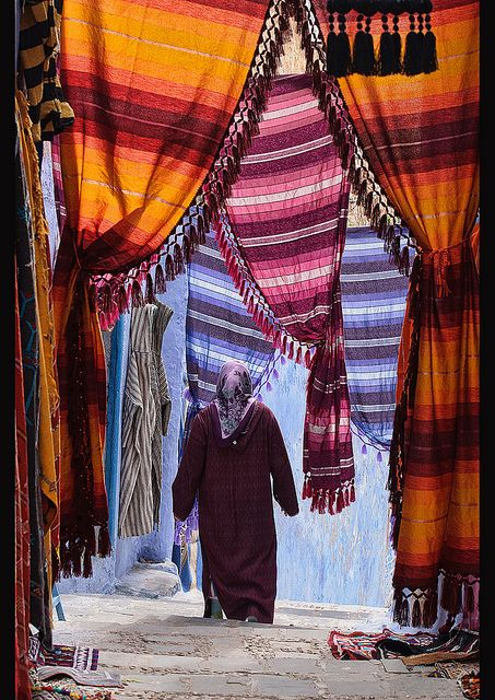 street of colorful tapestries in the atmospheric town of Chefchaouen, Morocco by jitenshaman, via Flickr