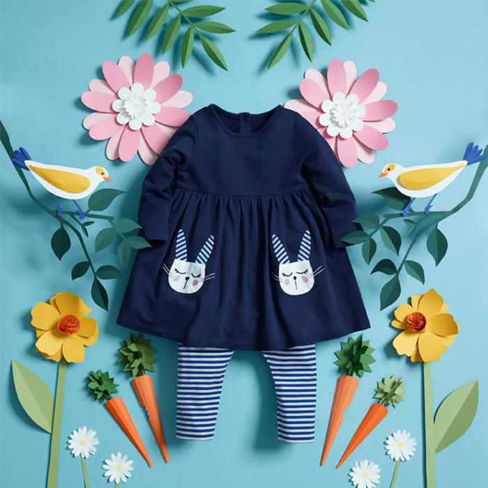 A girls' navy blue dress with rabbit detail pockets and striped blue and white leggings, surrounded by paper flowers