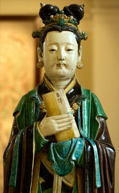 A judge's assistant.  She is holding a slender volume of good deeds.  Ming Dynasty (16th century) stoneware, British Museum.