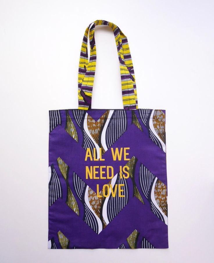 Tote bag en wax coloris violet et jaune, sérigraphié All we need is love coloris orange. Petit logo Goldensimone sérigraphié au dos du sac. de la boutique goldensimone sur Etsy