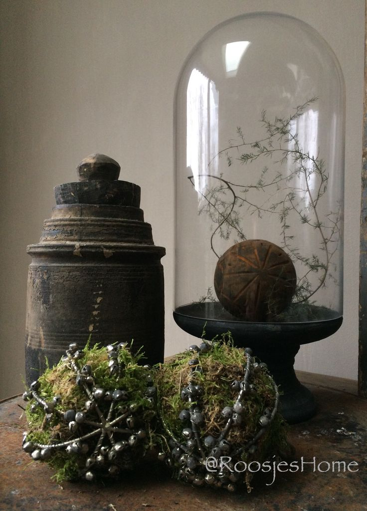 Stolp met een DIY roestige bal en asparagustak, gedecoreerd op een oud blik met belletjes mosballen en een oude pot