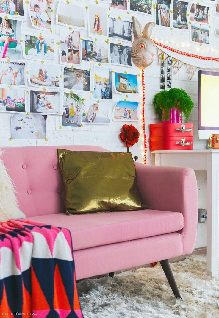 Essa sala tem decor inusitada e super aconchegante. Sofá rosinha e fotos na parede de tijolinhos, manta geométrica e tapete fofinho.