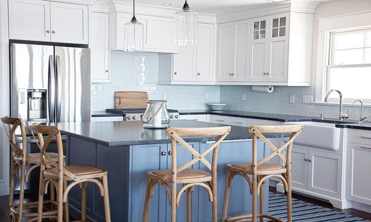 Stunning blue and white kitchen features a blue island painted Benjamin Moore Lava Blue and topped with honed black marble kitchen countertops surrounded on two sides by blond French x back cafe counter stools illuminated by glass cylinder light pendants.