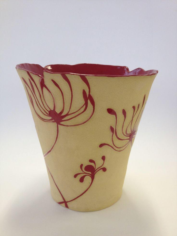 Ceramic vase with red flowers.