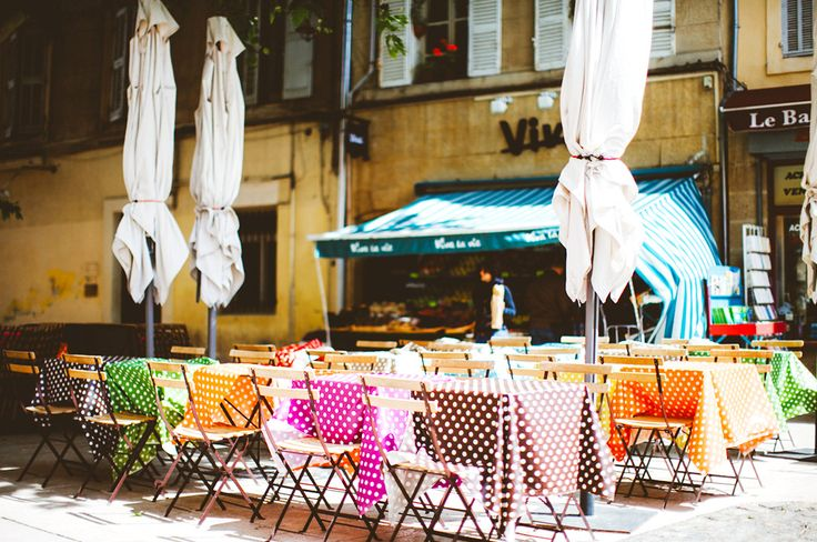 Outdoor tables with colorful, polka dot tablecloths outside of the restaurant