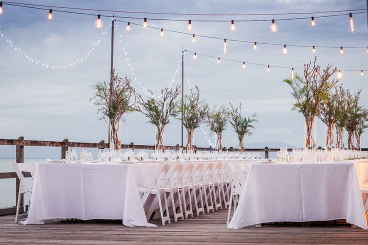 Sugar Wharf Port Douglas , alfresco wedding photography , Outdoor tropical decorations , fairy lights , gladiator Chairs , Beach ocean wedding , Cairns Queensland .  Destination paradise wedding . Alison Jones Photography .