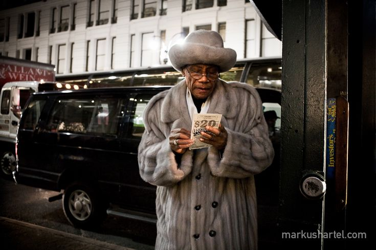Photography by Markus Hartel, New York: The soft lighting enhances the textures present within the image, particularly the texture of the subject's skin and coat. The gleaming white street light positioned directly behind the head of the subject causes the viewer to be immediately drawn to the man's face. The light grey fur coat and hat worn by the man cause him to look unique, the colour of his outfit allowing him to contrast the black van positioned in the background.