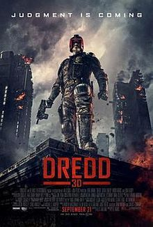 """A futuristic police officer in armour and a helmet that covers all but his mouth stands on the corner of a building roof with a gun in his hand as large tower blocks burn behind him. Above the man reads a tagline """"Judgment is Coming""""."""