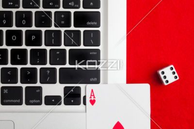poker online - Poker card, die and laptop suggesting playing poker online.
