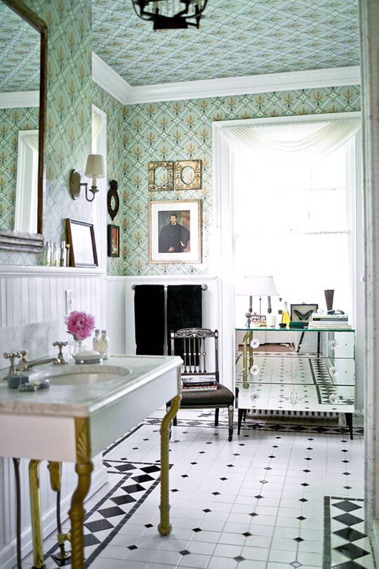 Green fleur-de-lis motif wallpaper from Brunschwig & Fils (on both walls and ceiling) is tempered by classic white woodwork and black accents in this master bath - Traditional Home®