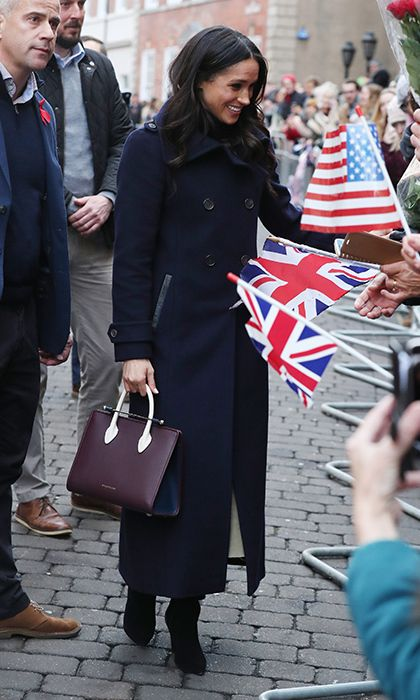 Joined by her husband-to-be Prince Harry, Meghan headed to Nottingham, England on December 1, for the royal couple's first public visit together since announcing their engagement. The former Suits actress looked stylish in a black turtleneck and beige Joseph skirt worn under her navy 'Elodie' coat by Canadian brand Mackage. Completing the look were black knee-high Kurt Geiger boots and a burgundy Strathberry purse.