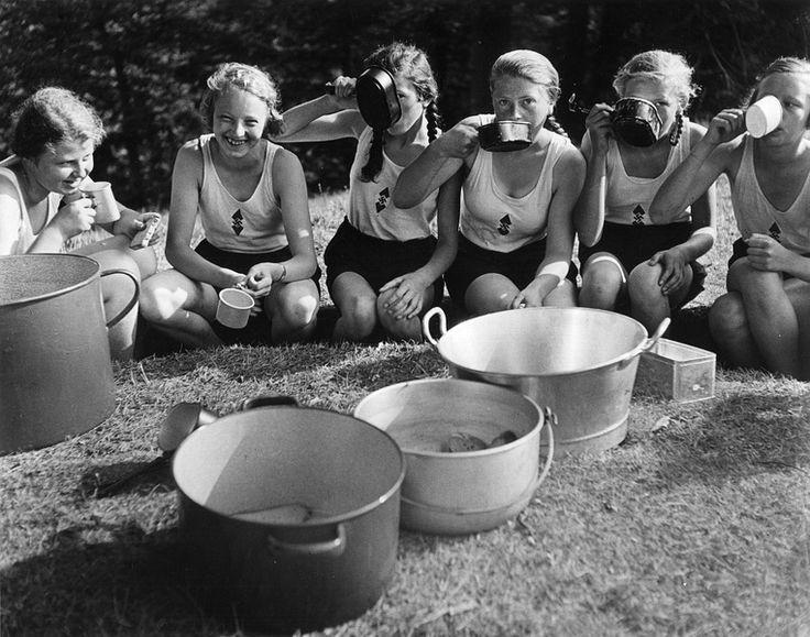 """Reinwarzhofen. Zeltlager des Bundes Deutscher Mädel (BdM) auf dem Zeltlagerplatz """"Göring-Espan"""". Mädchengruppe in Sportbekleidung, auf einer Wiese vor Töpfen sitzend und Tee trinkend - Deutsche Digitale Bibliothek"""