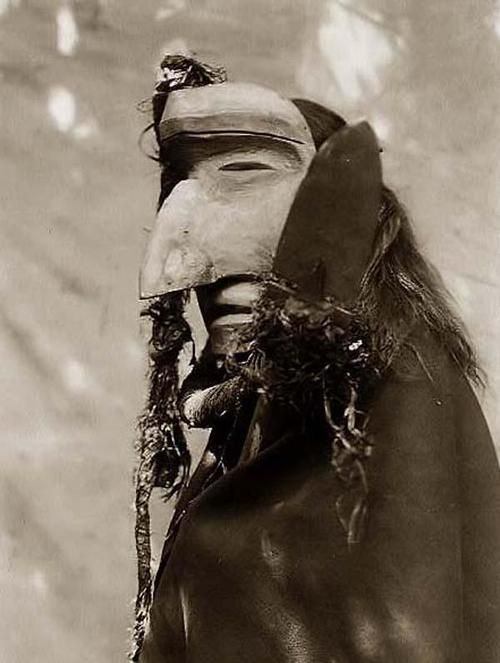 An impressive image of Nuhlimahla. It was taken in 1914 by Edward S. Curtis. The image shows a person wearing ceremonial mask of the Nuhlimahla during the during the Winter Dance ceremony. These characters impersonated fools and were noted for their devotion to filth and disorder.