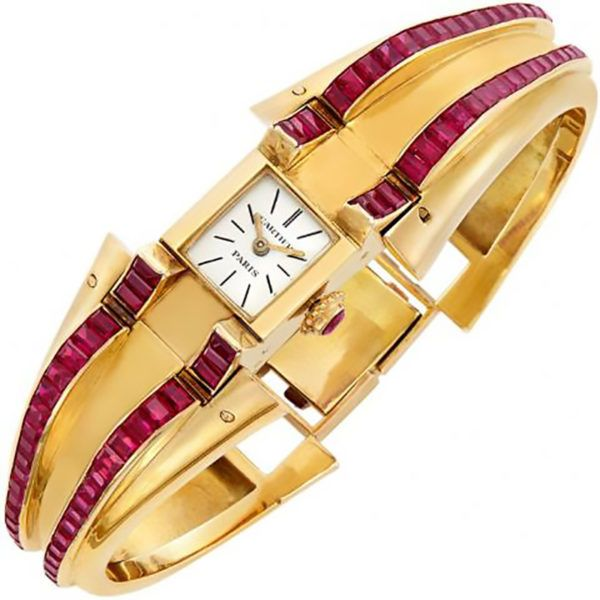 An 18kt yellow Gold and Synthetic Ruby Bangle-Watch by Cartier, Paris 18 kt., centering a rectangular-shaped white dial with black baton markers, with aftermarket round cabochon synthetic ruby crown, the hinged bangle with tapered bombe shoulders lined with two rows of square and rectangular-cut synthetic rubies, completed by a ruby-set clasp, dial signed Cartier, Paris, movement signed Cartier.