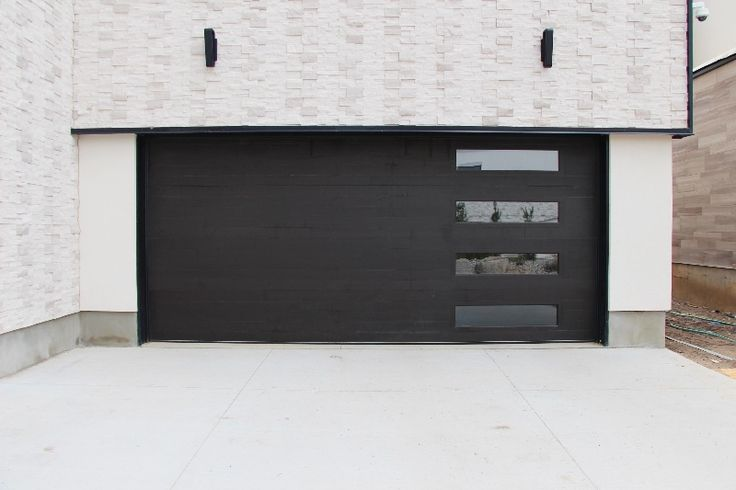 Contemporary Design Cedar Garage Door. Horizontal Inlay with Windows. Finished using Sansin custom color Stain. Oxford Carriage Door Ltd.
