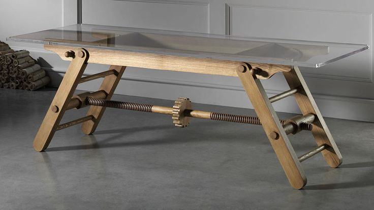 "Height adjustable table. "" my instinct would be to get down on all fours and crank that large gear in the middle by hand, to drive the threaded wooden rods and bring the legs closer together or further apart."""