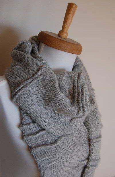 Оригинальный вязаный шарф выполнен спицами текстурной вязкой имитирующей складки.