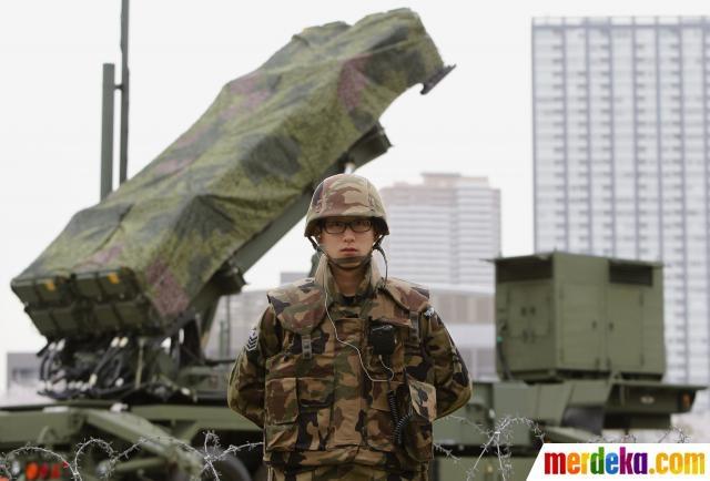 Seorang tentara Jepang berdiri dekat rudal Patriot di depan Kantor Kementerian Pertahanan di Tokyo Jepang Selasa (10/4).