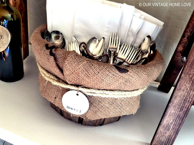 """old bushel basket and lined it with part of a coffee sack.  I tied a piece of rope around the overhang and attached this cute little merci clay tag to it.  Then filled it with our white cloth napkins and all the beautiful vintage flatware """"bouquets."""""""