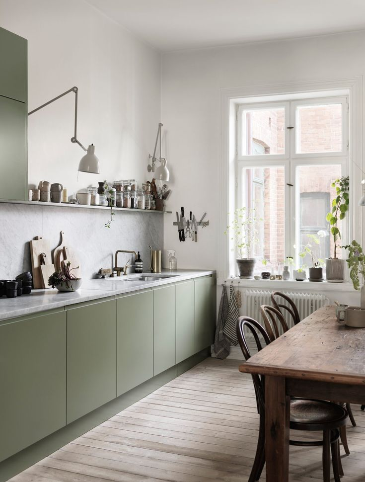 Kitchen with light green cabinets in a Scandinavian home